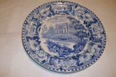 A Pearlware Blue Transfer Printed Pottery Plate printed with a scene showing the Fort at Allahbad with a river and tree in the foreground.