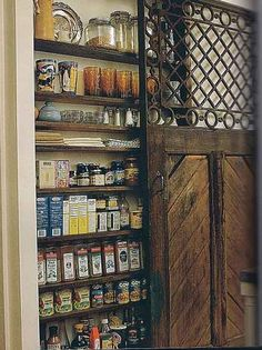 Beautiful one-can-deep pantry behind a wooden door. Using a small space for storage.