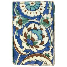 AN IZNIK POLYCHROME TILE, TURKEY, LATE 16TH-17TH CENTURY of rectangular form painted in underglaze cobalt blue, turquoise and relief red and outlined in black with a composite lotus palmette enclosed by arching stems issuing buds, saz leaves and a large composite rosette