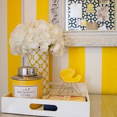 Fun yellow office with white & yellow vertical stripes walls, gray ornate mirror, glossy white lacquer tray and yellow vase. Yellow Office, White Office, Vases Decor, Table Decorations, Yellow Accents, Yellow Stripes, Paint Stripes, Candy Stripes, Vase With Lights