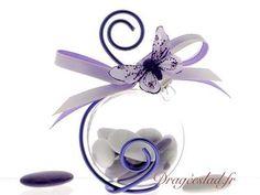 Boule transparente tendance décorée de son papillon cristal lilas et garnie de dragées mariage. Le fil aluminium est travaillé de façon très original autour de la boule. Boule dragées sur Dragéeslad.