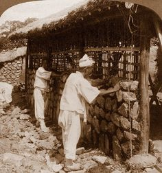OLD KOREA - LAND OF THE MORNING CALM -- Sticks, Mud, Rock, and Rope. Building a Home in SEOUL - Photo by HERBERT G. PONTING, 1903.