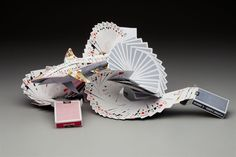 """Hannah Kim -- """"Card Shark"""" Mixed media - playing cards and wire """"Influenced by the sculpture at the Fluor Daniel Engineering Building at Clemson University, I overlapped the playing cards to create a wave-like pattern and connected it with the repetition in the shark as well. I wanted to create a piece that translated the whimsicality of the pun, 'card shark,' by morphing the deck of cards into a sculptural shark coming out of waves of playing cards."""" -- Coppell High School;"""