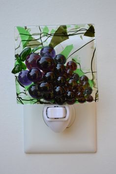 This fused glass night light features a bunch of purple grapes (glass), fused onto a piece of glass, approximately 3 square, background of glass with green and black confetti and streamers running through it. The glass was fused in my kiln, and then attached to a white night light fixture, with an on/ off switch, so that you can turn the light on and off, as needed.