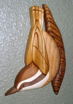 Intarsia Nuthatch Bird. The wood: walnut: beak, feet, and dark stripe in head. aspen: white stripes in head. western red cedar: top of head, upper body/feathers. red oak: belly. zebra wood: branch