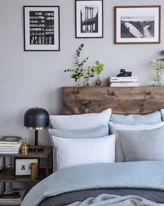 Love this simple but natural backboard. Blue grey and brown bedroom. Black and white pictures above bed. Black lamp on side table. Stack of books. Bedroom.