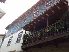 Casa de portadas vermelhas e painéis de xisto na parede exterior