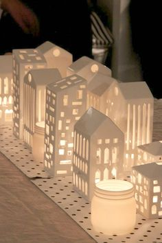 "Make ""village"" buildings out of cardboard/modge podge then paint... use flameless candles or lights inside then real candles (in votives) outside of the buildings!"
