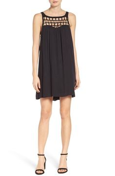 A crocheted neckline defines this lightweight shift dress that pairs perfectly with black heels.