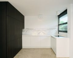 Custom made kitchen with dark wood, and white marble by German company Holzrausch.