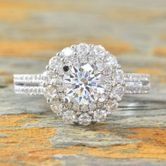 """A dazzling double diamond wraps around the center mounting of this rondels, 18k white gold, engagement ring with sparkling split shank. Set with round diamonds total weight: 0.80ct , Color: E-F Clarity: VS-SI. Center Stone Options: Certified GIA Round Diamond 1.00ct Moissanite Forever One """"Charles & Colvard"""" 6.5mm Round Brilliant Cut Diamond *All purchases come with an Appraisal stating the retail insurance replacement value of double your checkout price. Made to Order, please allow 3-4…"""