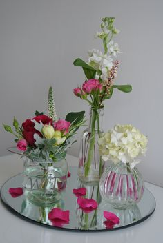 Jam jars & bottles with flowers on mirrored disk.