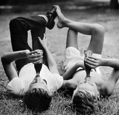 Laying in a park, drinking a cola with feet touching -