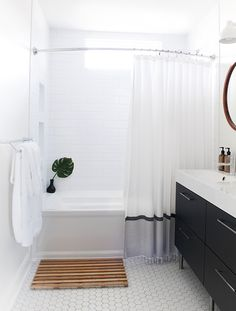 black and white trimmed shower curtain in black and white bathroom