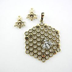 Awesome set that includes a two-tone metal pendant and charms. The pendant is a gold-tone metal honeycomb with a small silver-tone bee