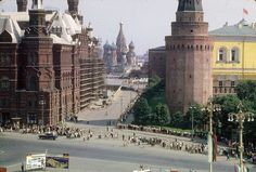 An entrance to Moscow's Red Square, with St. Basil's Cathedral in the distance, and the State Historical Museum to the left. Thousands of people can be seen standing in a long, snaking line to enter Lenin's mausoleum.