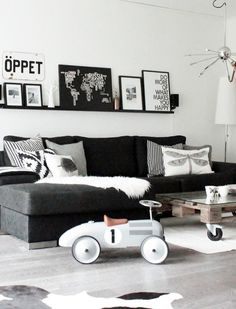 black and white living room - clean lines of couch softened with mix of scatter cushions and upcycled pallet coffee table. Interesting way to display artwork on a shelf rather than hung on the wall - allows for easy changes