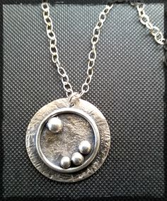 """Orbit"" Necklace. Reticulated silver over copper, with fine silver accents. Oxidized in a solution of liver of sulphur and ammonia to bring out subtle hints of blue and gold. The disk is 2 1/8"" in diameter and hangs from a 17"" sterling chain that is finished with a spring ring clasp."