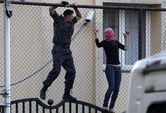 Un policier (G) essaie d'attraper une supportrice du groupe de punk Pussy Riot dans l'ambassade de Turquie située près du tribunal de Moscou (Russie), le 17 aoît 2012. ALEXANDER ZEMLIANICHENKO