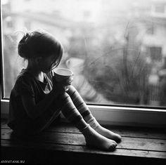 Маленькая девочка грустит у окна. Черно-белые фото