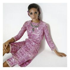 Vogue - January 1969 Photographic Print by Gianni Penati.  Marisa Berenson lounges on the floor of an all-white studio. Clad in a mauve lamé Indian tunic-and-pants set by Chanel, she manages to look exotic in the most mundane of locales. Berenson's ability to transform herself into a number of characters became her legacy.