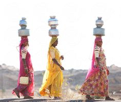 Indian women carrying water jugs to their homes. by Hugh Sitton - Stocksy United