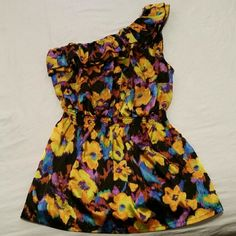 Gorgeous Silky One Shoulder Ruffle Tunic Tank You will definitely stand out in this amazing floral top this summer! It has a silky sheen to it and the jewel-toned flower pattern is so elegant. It is brand new, never worn. Curen Sport Tops Tank Tops