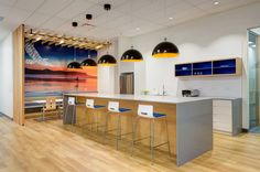 Lunchroom at Golder Associates - office interior design by SSDG Interiors Inc. - wood flooring, lunch counter, pendant lighting, wood surround, wall graphic, modern office design