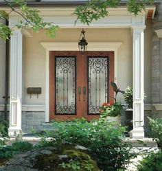 Decorative wrought iron overlays frosted glass (inset in wood) for this beautiful double-door entryway. Iron provides a unique look as well as added security.