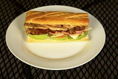 Three Little Pigs Torta: Pork loin, black forest ham and applewood smoked bacon served on a toasted French bread roll with beans, tomatoes, onions, jalapeño  peppers, chipotle mayo, lettuce, Swiss cheese and avocado. @ Manny's Tortas