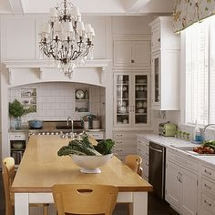 I love the chandelier in the middle of the kitchen.....don't like the black appliances against the white cabinets.