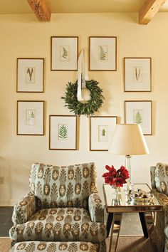 Seasonal Wall Art - 54 Festive Christmas Wreaths - Southernliving. Rearrange your prints like these botanicals for the season to make room for a wreath. Simply tie it with a knot of satin ribbon.