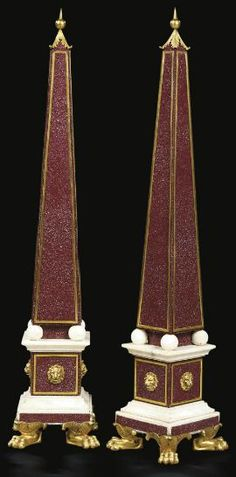 A PAIR OF ITALIAN ORMOLU-MOUNTED, PORPHYRY AND WHITE MARBLE OBELISKS 19TH CENTURY, LATER MOUNTED Each of typical form, with foliate-cast pricket finial, on ball feet, above a panelled plinth mounted with lion masks and a square stepped plinth base, on foliate-wrapped paw feet 45¾ in. (116 cm.) high; (2)
