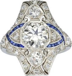 Art Deco Diamond, Sapphire, Platinum Ring  The ring features a transitional round brilliant-cut diamond measuring 7.40 - 7.35 x 4.10 mm and weighing approximately 1.35 carats, enhanced by mine and single-cut diamonds weighing a total of approximately 1.25 carats, accented by fancy-cut sapphires, set in platinum. Total diamond weight is approximately 2.60 carats. Gross weight 6.80 grams.