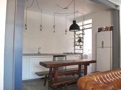 Cozinha com armario e painel azul mineral. Mesa TCouto. Luminária Muuto. Iluminação com pendentes. Bancada e estrutura interna em concreto, moldados manualmente na obra. Piso em cimento queimado. Arvorar Estúdio.