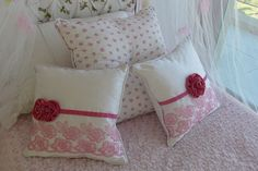 Románticos almohadones con apliques de flores en dos tonos de rosa; detrás, uno estampado y otro en blanco puro (desde $280, Antique Nouveau).