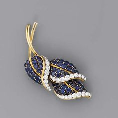 A SAPPHIRE AND DIAMOND BROOCH, BY VAN CLEEF & ARPELS The three stylised leaves set with circular-cut sapphires and diamond part border, circa 1960, 6.9 cm. high, with French assay mark for gold