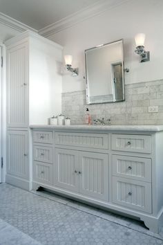 The vanity features custom millwork with beadboard inset panels. Marble tile and metallic fixtures complete the pristine look.