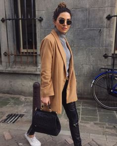 Warm camel coat, grey turtleneck sweater, leather pants. Fall wear perfected.