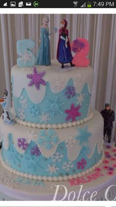 Frozen cake... And why is this the exact same ages that my girls are turning this year at tier frozen party. Fate.