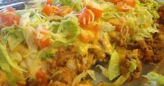 7oz. bag Nacho Cheese Doritos, crushed 1 lb lean or extra lean ground beef 1/2 cup diced onion (optional) 1 pkg. taco seasoni...