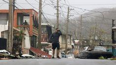 A man reacts as he walks through a debris-covered road in Fajardo, Puerto Rico.
