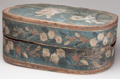 """POLYCHROME PAINT-DECORATED PINE BRIDE'S BOX, oval bentwood form, top featuring a landscape comprising three figures and trees with an illegible inscription above, running floral decoration surrounding sides. 18th or 19th century. 9"""" H, 14 1/2"""" x 21""""."""
