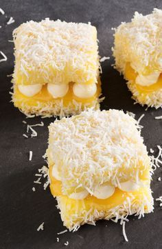 These deliciously light lemon meringue lamingtons (or lemingtons as we like to call them) are filled with tangy lemon curd and creamy meringue buttercream and coated in shredded coconut. Zumbo's Just Desserts, Mini Desserts, Delicious Desserts, Dessert Recipes, Classic Desserts, Plated Desserts, Cupcake Recipes, Lemon Recipes, Baking Recipes