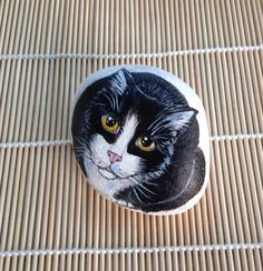 Black and white cat hand painted on a pebble by TheDandyArtist