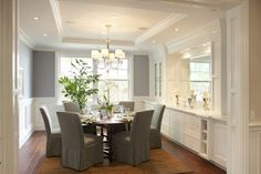 Walls in Benjamin Moore's Solitude AF-545 pop against the white wainscoting and built-in dining banquette.