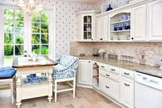 beige granite countertop with whitewashed brick backsplash and ivory corner upper cabinet with glass inserts and rope molding with pull-out wicker storage baskets and two-tiered breakfast table with blue and white settee