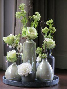 Verschillende vaasjes opgemaakt met zijden bloemen in groen/wit tinten. www.abonneefleur.nl