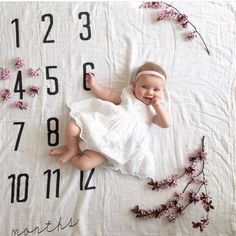 beautiful baby // 4 months old on our monthly milestone blanket. Flowers make it feel like spring. She is just darling.