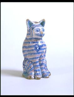 Delftware. Drinking vessel in the form of a cat with painted stripes and an inscription, tin-glazed earthenware, England, 1676.